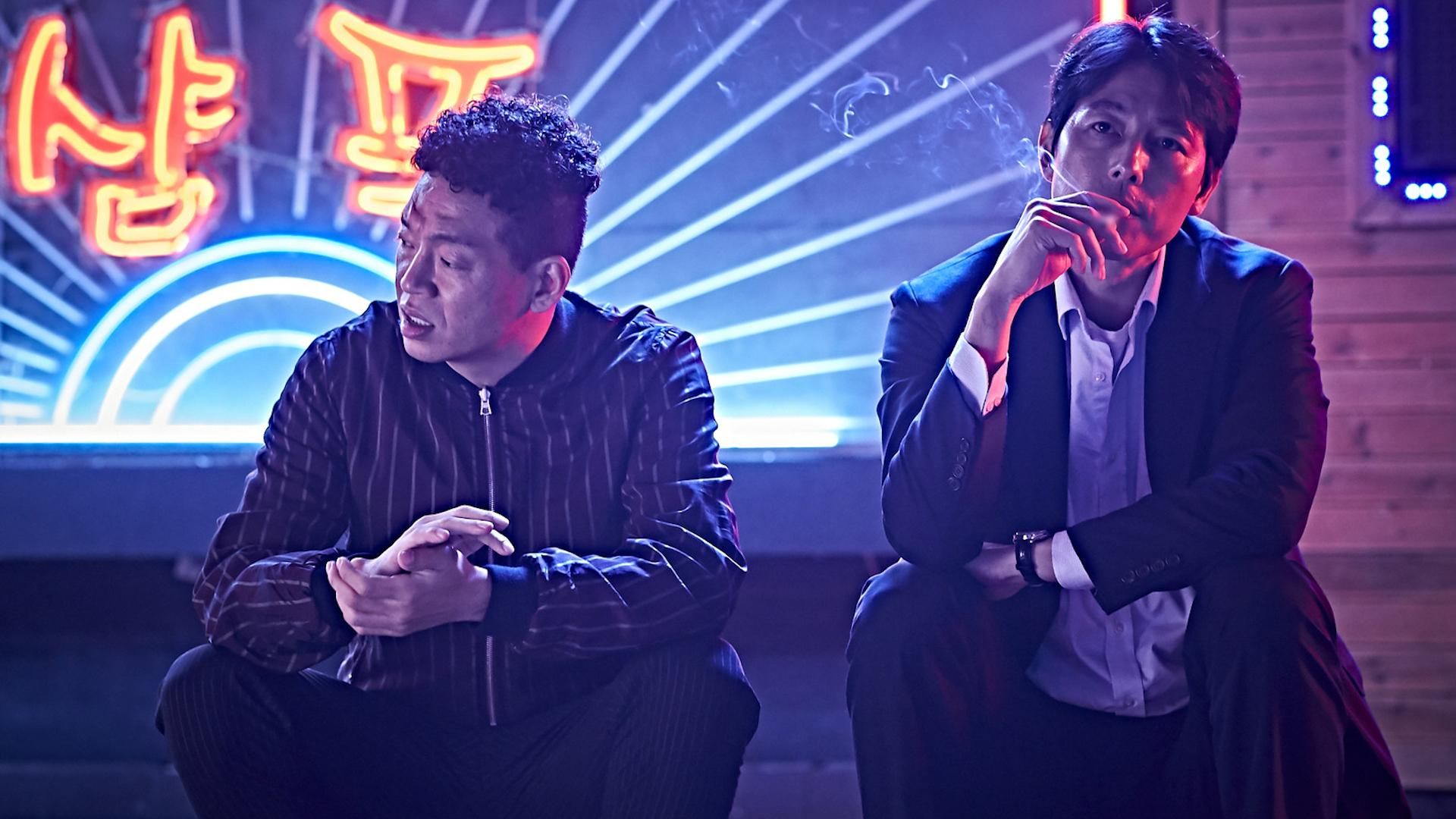 A man in a track jacket and another man smoking in a suit sit in front of a neon sign in Beasts Clawing at Straws.